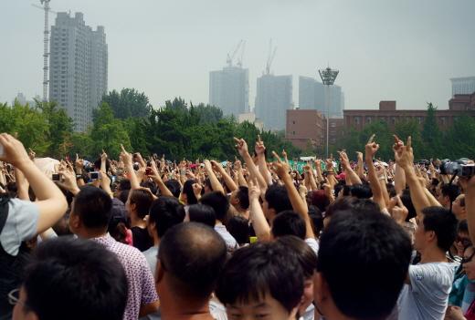 지난 14일 다롄 시민들이 푸자 화학공장 건물 인근에 모여 가운데 손가락을 치켜들며 '나가라'고 항의하고 있다. | STR/AFP/Getty Images