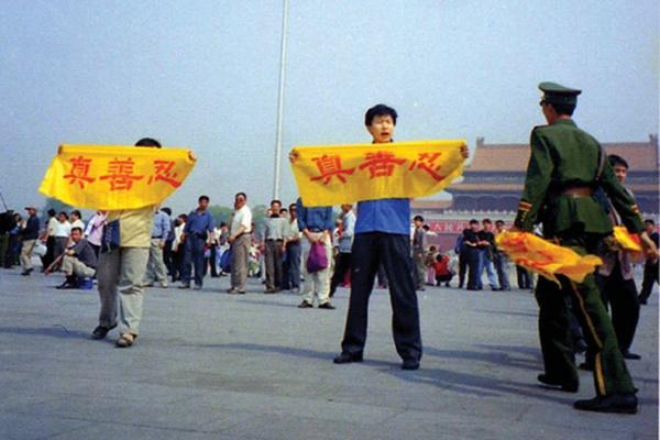 파룬궁 수련자들이 베이징 톈언먼 광장에서 평화롭게 진(眞), 선(善), 인(忍) 현수막을 펼쳐 파룬궁 진상을 알리는 것을 공안이 저지하고 있다. | 밍후이왕