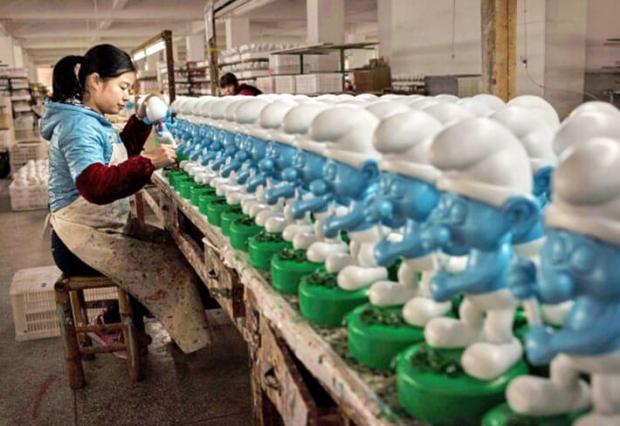 2014년 12월 7일 중국 푸젠성의 한 공장에서 중국인 노동자가 도자기로 된 스머프에 색을 칠하고 있다. | KEVIN FRAYER/GETTY IMAGES