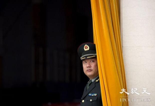 중국 인민해방군인이 2011년 12월 25일 베이징 인민대회당의 커튼 뒤에서 대기 중이다. | Ed Jones/AFP