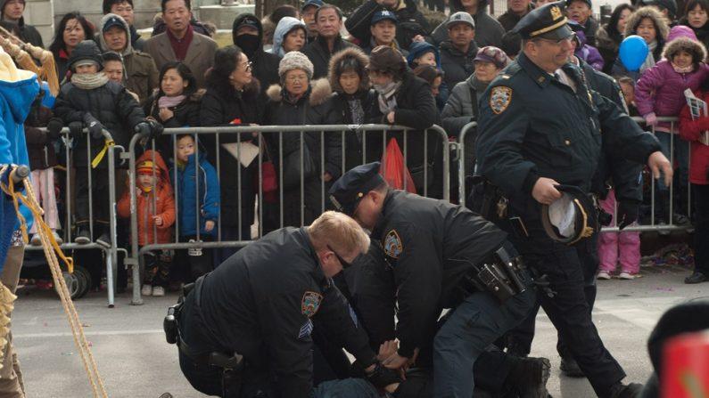 2011년 2월 12일, 미국 뉴욕 플러싱에서 한 중국계 남성이 파룬궁 퍼레이드 행렬에 뛰어들어 현수막을 훼손시켰다. 3명의 경찰이 그들을 제압하고 체포했다.   에포크타임스 DB