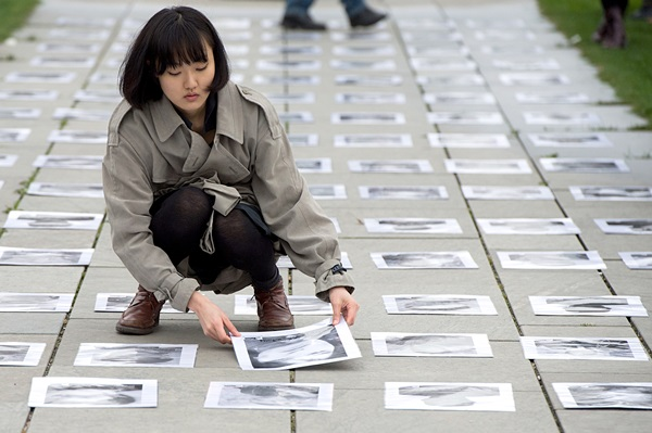 해외 망명한 티베트인 여성이 독일 베를린 총리공관 앞에서 중국 당국에 항의해  분신자살한 티베트족의 사진을 바닥에 펼쳐놓고 있다. | AP/연합