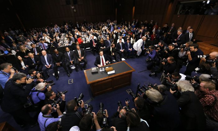 """2017년 6월 8일, 전 FBI 국장 제임스 코미가 워싱턴에 위치한 미국 의회에서 열린 """"러시아 정부의 2016년 미국 대선 개입 의혹""""에 대한 상원 정보 위원회의 청문회에서 증인 선서를 준비하고 있다.   REUTERS/Jim Bourg"""