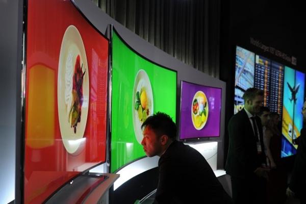 2014년 1월 8일 라스베가스에서 열린 2014 국제 소비자 가전쇼의 한 관람객이 LG의 105인치 OLED TV를 자세히 살펴보고 있다.   Robyn Beck / AFP / Getty Images