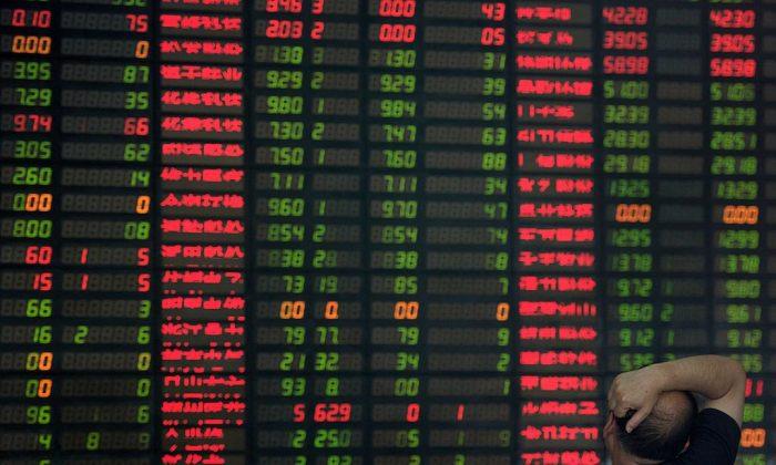2015년 9월 1일, 한 투자자가 상하이 소재 증권회사에서 주식 시장 전광판을 바라보고 있다.   Johannes Eisele/AFP/Getty Images