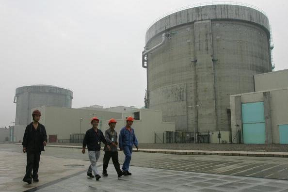 2005년 6월 10일, 저장성 자싱시에 위치한 친샨 원자력발전소 근로자들이 원자로 격납구조물 옆을 지나고 있다. | Frederic J. Brown/AFP/Getty Images