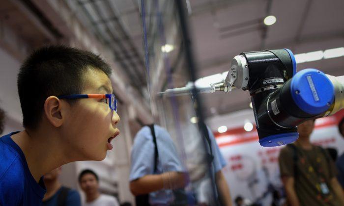 베이징에서 2018년 8월 15일 개막한 2018 세계로봇대회에서 한 소년이 로봇 암을 바라보고 있다.   Wang Zhao/AFP/Getty Images