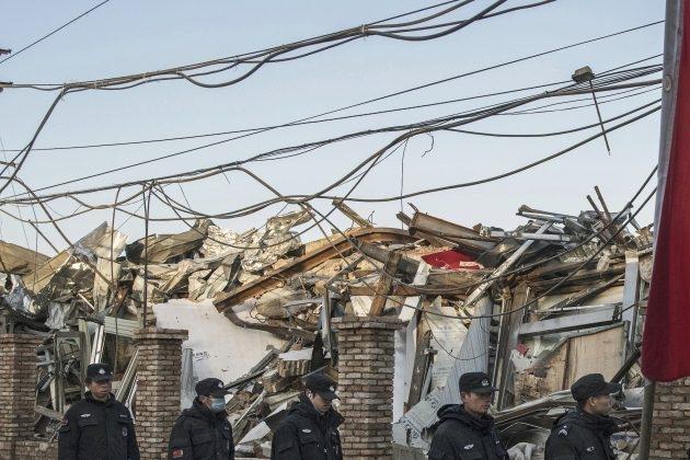 중국 경찰이 이주자 주택과 공장들이 있었던 중국 베이징의 다싱구에서 당국이 철거한 건물들 옆으로 줄 지어 걸어 가고 있다. 2017년 12월 6일 | Kevin Frayer/Getty Images