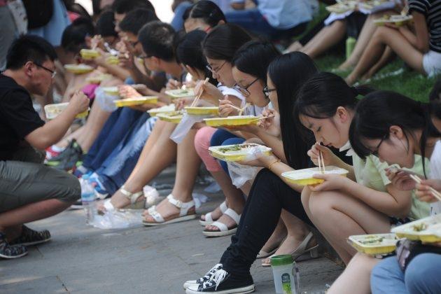 2015년 7월 29일, 중국 산둥성 지난에서 대학원 지원자들이 강당 밖 바닥에 앉아 식사를 하고 있다. | VCG/VCG via Getty Images