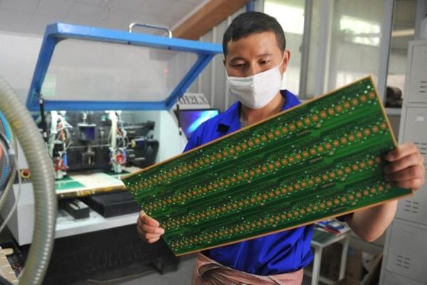 2018년 5월 22일, 중국 동부의 저장성 항저우에 위치한 공장에서 한 노동자가 회로판을 점검하고 있다.   AFP/Getty Images