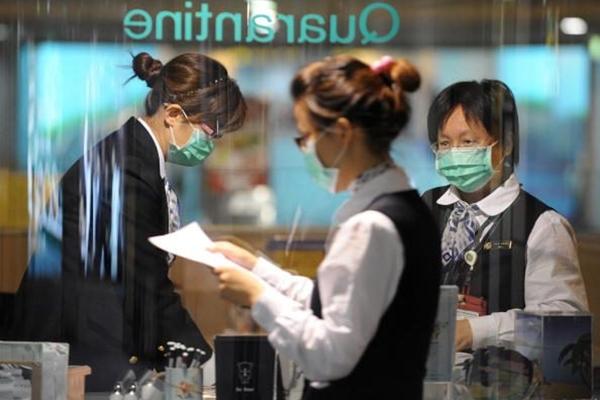 2009년 4월 28일, 타오위안 국제공항의 검색대 옆 마스크를 착용한 타이완 정부소속 검역관들의 모습.(Sam Yeh/AFP/Getty Images)