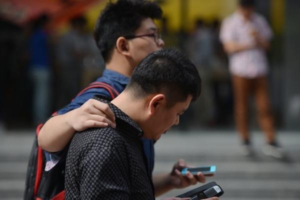 중국 시민들이 길을 가며 스마트폰을 보고 있다. 2013년 9월 25일 상하이의 어느 거리. (PETER PARKS/AFP/Getty Images)