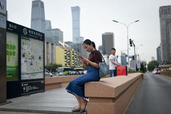 어떤 여성이 베이징의 한 지하도 입구에서 휴대폰을 사용하고 있다. (2018년 9월 18일) (Wang Zhao/AFP/Getty Images)