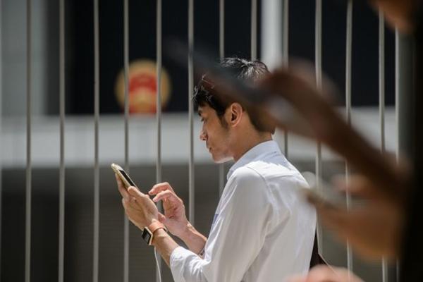 2016년 7월 26일, 홍콩 입법부 건물 밖에서 스마트폰을 보고 있는 사람들| Anthony Wallace/AFP/Getty Images