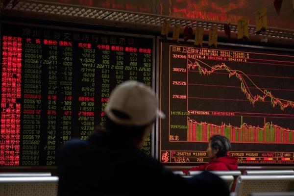 베이징의 한 증권사에서 투자자가 주식 시황판을 주시하고 있다. 2018년 10월 11일.   NICOLAS ASFOURI/AFP/Getty Images