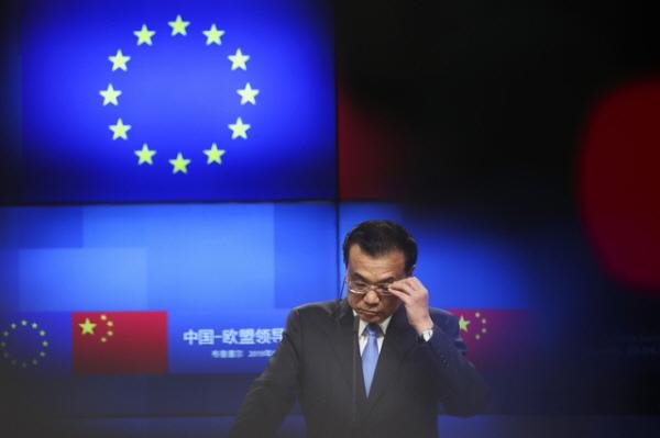 4월9일(현지시간) 벨기에 브뤼셀에서 열린 유럽연합(EU) 중국 정상회의에서 리커창 중국 총리가 EU의 도날트 투스크 정상회의 상임의장 및 장-끌로드 융커 집행위원장과의 공동 기자회견장에서 안경을 만지고 있다.(AP/뉴시스)