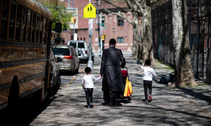 2019 년 4 월 24 일 한 유대인 남자가 뉴욕시 윌리엄스 버그 브루클린에 있는 유대인 지구 거리를 따라 아이를 데리고 걸어 간다.(Johannes Eisele / AFP / Getty Images)