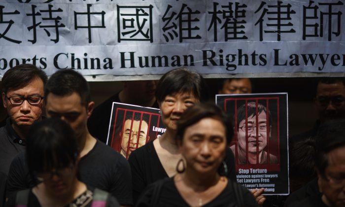 홍콩 민주화 운동가들이 2017년 7월 9일 홍콩 종심법원(終審法院) 밖에서, 구금 중인 중국 인권변호사 졘톈용과 왕취안장의 초상을 들고 중국 인권변호사들을 지지하는 침묵 시위를 하고  있다. 이날 모인 수십 명의 홍콩 시민은 2015년 7월 9일 중국에서 일어난 인권변호사들에 대한 대대적 탄압을 기억하며 그들에 대한 연대를 표명하기 위해 홍콩 종심법원 앞에 모여 7분 9초간 묵념하고 있다. | TENGKU BAHAR/AFP/Getty Images