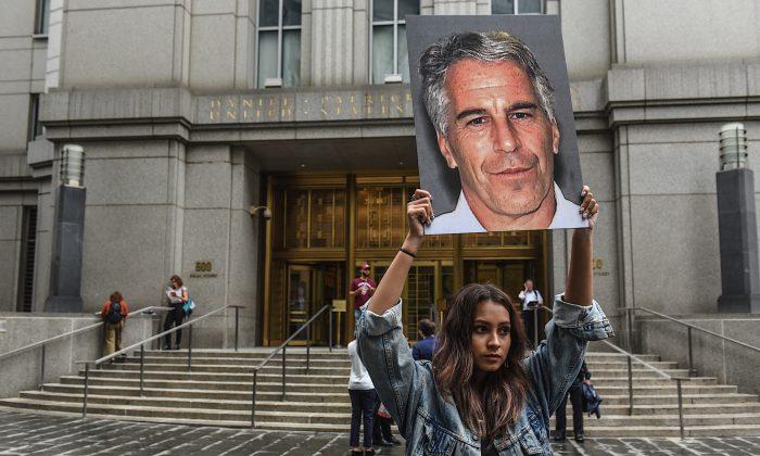 미국 뉴욕의 연방법원 정문 앞에 한 시위자가 제프리 엡스타인의 사진을 들고 있다. 2019.7.8   Stephanie Keith/Getty Images