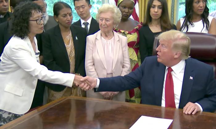 트럼프 대통령이 중국의 종교박해에서 생존한 파룬궁 수련자 장위화씨와 백악관 집무실에서 악수하고 있다. 이 자리에는 전 세계 17개국 종교박해 생존자들이 초청됐다. 2019.7.17 | Chip Somodevilla/Getty Images