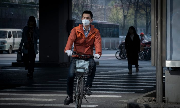 베이징에서 자전거 타는 사람이 대기오염의 영향을 줄이기 위해 보호 마스크를 쓰고 있다. 2019.3.27. | Nicolas Asfouri/AFP/Getty Images