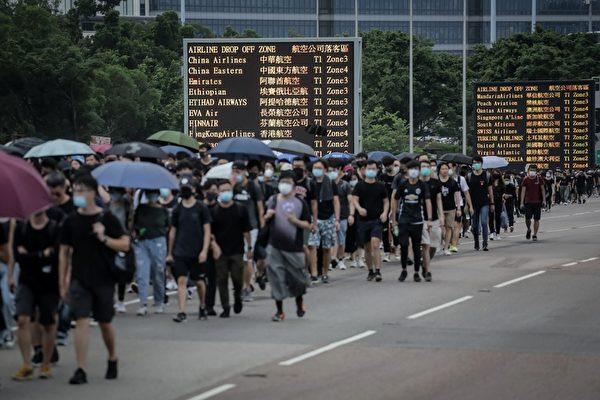 12일 홍콩국제공항에서 이동하고 있는 송환법 반대 시위대 | VIVEK PRAKASH/AFP