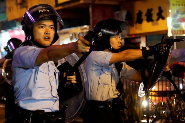 25일 홍콩 췬완 지역에서 홍콩 경찰이 시위대를 향해 권총 정조준 하고 있다. | REUTER=Yonhapnews(연합뉴스)