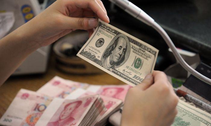 중국 안후이성 허베이시의 한 은행 카운터에서 중국인 은행원이 100위안짜리 지폐 뭉치와 미국 100달러 지폐를 확인하고 있다. 2010.9.30   STR/AFP/Getty Images