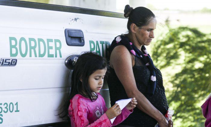 멕시코에서 리오그란데 강을 건너 미국 국경을 불법 횡단한 혐의로 체포된 만삭의 임산부와 한 소녀가 국경 순찰 트럭에 몸을 기대고 있다. 텍사스주 매캘런 인근. 2019.4.18. | Charlotte Cuthbertson/The Epoch Times