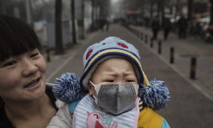 베이징 시내에서 한 여성이 아기에게 마스크를 씌워서 외출했다. 2015.11.8. | Kevin Frayer/Getty Images