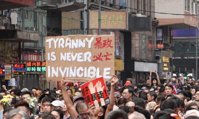 """홍콩 시위대가 캐리 람 정부에 대항해 """"폭정은 결코 천하무적이 아니다""""라고 적힌 팻말과 """"어린이들은 폭도가 아니다""""라는 붉은색 팻말을 들고 있다. 2019.6.16.   Yu Gang/The Epoch Times"""