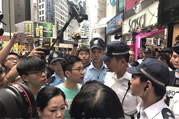 네이선 로(羅冠聰), 조슈아 웡(黃之鋒) 등이 코즈웨이 베이 소고(SOGO) 옆에서 경찰과 논쟁하고 있다. 그들은 경찰의 권한이 과대하여 평화시위를 저애하고 있다고 비판했다.   린이(林怡)/에포크타임스