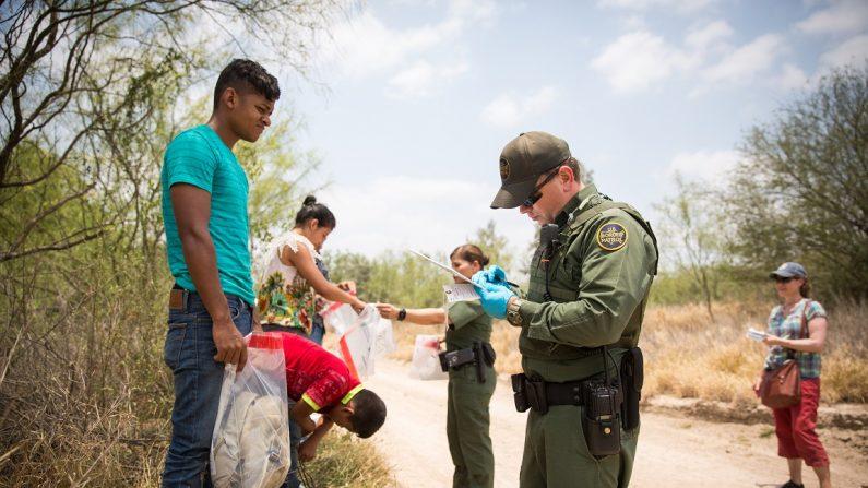 텍사스주 이달고 카운티에서 국경순찰대가 불법 입국자들을 수송용 승합차에 탑승시키기 전 신발 끈과 소지품을 수거하고 있다. 2017. 5. 26. | Benjamin Chasteen/The Epoch Times