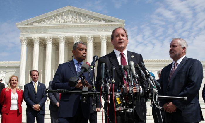 켄 팍스턴 텍사스 검찰총장이 미국 연방 대법원 앞에서 기자회견을 갖고 발언하는 중에 워싱턴 검찰총장 칼 라신이 오른쪽에서 듣고 있다. 2019.9.9.   Alex Wong/Getty Images