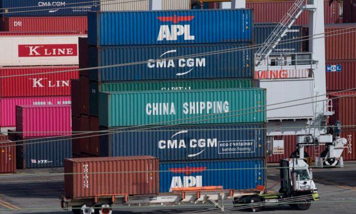 트럼프 대통령이 중국 수입품에 새로운 관세를 부과한 뒤 로스앤젤레스 항구에서 트럭이 선적 컨테이너를 지나가고 있다. 2019. 9. 1.   MARK RALSTON/AFP/Getty Images