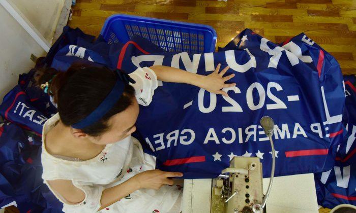 중국인 근로자가 도널드 트럼프 대통령의 2020년 미국 대선 캠페인 배너를 만들고 있다. 중국 안후이성 푸양의 한 공장에서 촬영  2018.7.13 |AFP/Getty Images
