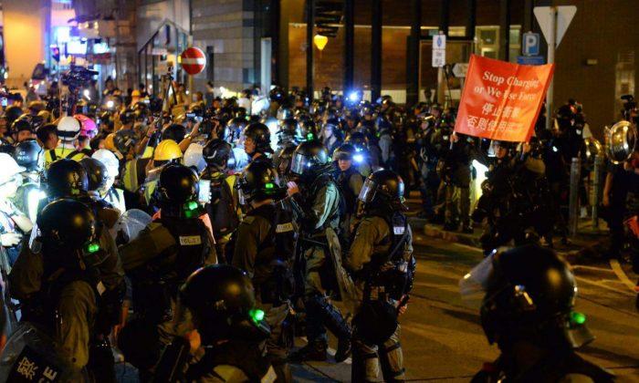 홍콩 시위대와 충돌하는 시위 진압 경찰이 붉은 경고 깃발을 들어 보인다. 2019. 9. 7. | Sung Pi Lung/The Epoch Times
