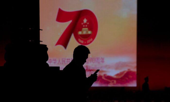 베이징 거리에 설치된 한 대형 스크린에서 공산 정권 수립 70주년 기념 영상이 상영되는 가운데 한 남성이 휴대전화를 사용하고 있다. 2019.9.26ㅣNoel Celis/AFP/Getty Images