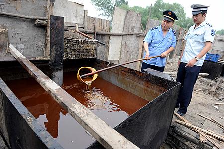경찰이 베이징에서 단속 중에 압수한 불법 식용유를 검사하고 있다. 2010. 8. 2 | STR/AFP/Getty Images