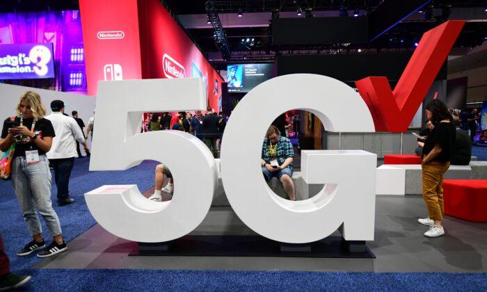 미국 캘리포니아 주 로스앤젤레스에서 열린 박람회 E3(Electronic Entertainment Expo)에서 휴대전화 사용자들이 버라이즌 5G 디스플레이 옆에 서 있다. 2019. 6. 12. | Frederic J. Brown/AFP/Getty Images