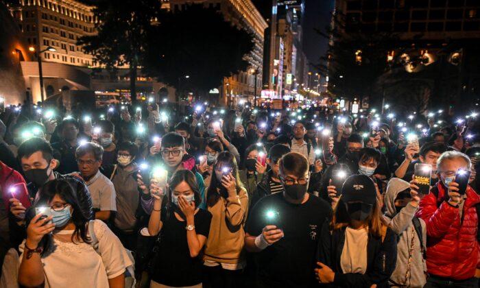 홍콩 경찰에 의해 전면 봉쇄된 홍콩 이공대 내 학생들을 위해 사람들이 휴대전화를 들고 기도하고 있다. 2019.11.19 | YE AUNG THU/AFP via Getty Images
