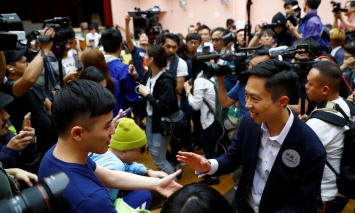 지역 후보 켈빈 램이 홍콩 사우스 호라이즌스 웨스트 구역의 한 투표소에서 자신의 지역구 지방의회 선거에서 승리했다는 발표가 있은 후 지지자들과 함께 축하하고 있다. 2019. 11. 25. | Thomas Peter/Reuters