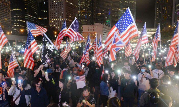 홍콩 에든버러 집회에 참석한 시위대가 미국 국기를 흔들며 휴대전화 플래시를 들고 있다. 2019. 11. 28. | Sung Pi Lung/The Epoch Times