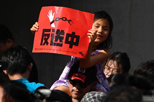 아버지의 어깨에 어린 소녀는 2019 년 6 월 16 일 논란이되고있는 인도 법안에 반대하며 홍콩에서 계속되는 항의 시위를 지원하기 위해 타이페이 시위에서 현수막을 들고있다. | Sam Yeh/AFP/Getty Images