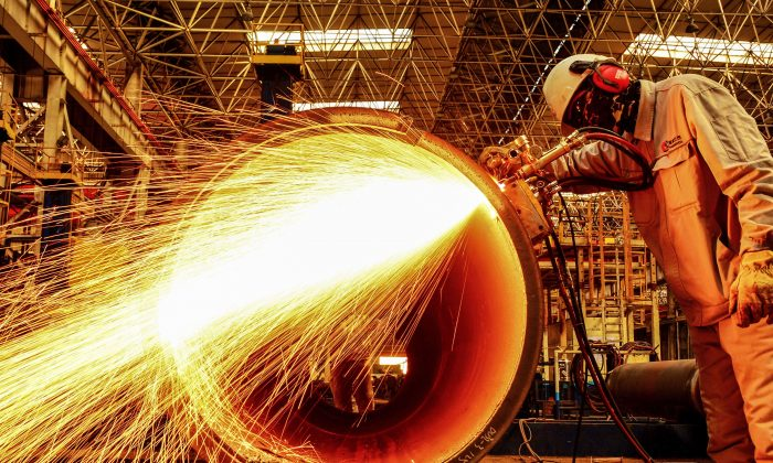 2019년 2월 28일 중국 산둥(山東)성 칭다오(靑島)의 한 공장에서 한 근로자가 송유관을 절단하고 있다. 2월 28일 공식 자료에 따르면 중국의 제조업 활동이 2월 들어 3개월 연속 감소해 경기가 침체되고 미국의 무역전쟁에 물들면서 3년 만에 최악의 실적을 기록했다. | STR/AFP/Getty Images