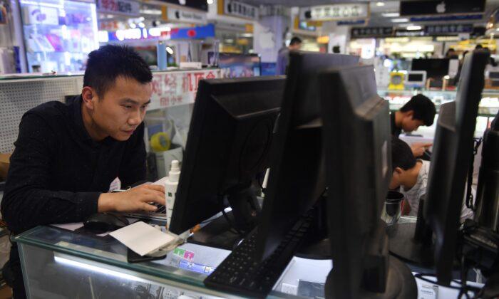 베이징의 컴퓨터 매장에서 한 남성이 노트북을 수리하고 있다. 2018. 3. 30. | GREG BAKER/AFP via Getty Images