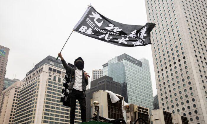 홍콩 중심가 에든버러 광장에서 집회가 열리는 동안 주차장 꼭대기에서 시위자가 깃발을 흔들고 있다. 2019. 12. 29.   Isaac Lawrence/AFP with Getty Images