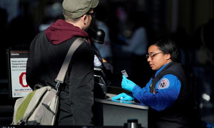 미국 교통안전국(TSA) 직원이 레이건 내셔널 공항에서 한 여행자의 서류를 확인하고 있다. 2019.1.6.|Joshua Roberts/Reuters=Yonhapnews(연합뉴스)