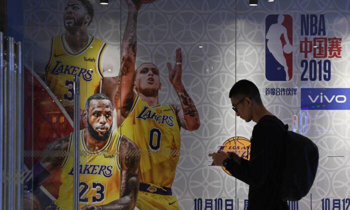 베이징 미국프로농구(NBA) 매장에 붙은 LA 레이커스와 브루클린 네츠의 중국 시범경기 광고 앞을 한 남성이 지나가고 있다. 2019. 10. 9. | Greg Baker/AFP, Getty Images