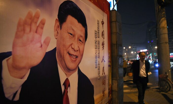 베이징에서 열린 제19차 공산당대회 폐막 후 한 남성이 길가의 시진핑 중국 국가주석의 포스터 앞을 지나가고 있다. 2017. 10. 24.   GREG BAKER/AFP via Getty Images